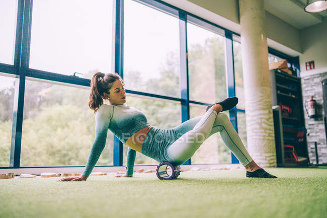 Side view of barefoot slim woman in sportswear performing abdominal crunches on foam roller against window in gym — Stock Photo