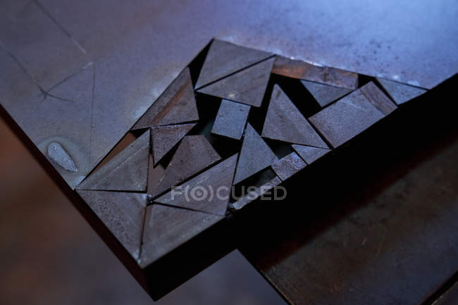 Closeup of metal sheet with part cut into geometric pieces — Stock Photo