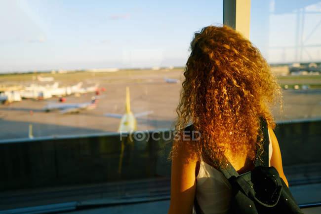 Vue arrière de la femme élégante bouclée avec sac à dos observatoire terrain avec des avions à l'aéroport de Texas — Photo de stock