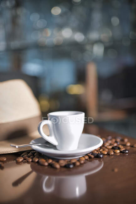 Cups of tasty hot drink in composition with hat and coffee beans on wooden table — Stock Photo