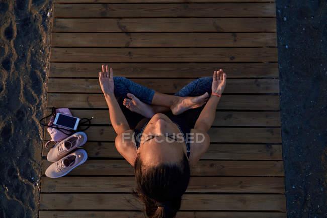 Desde arriba de la mujer descalzo en el sudor deportivo sentado en loto posan en el camino de la madera cerca de los zapatillas y el teléfono inteligente y la meditación. - foto de stock