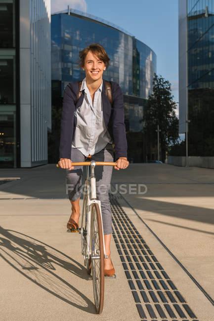 Восхитительная женщина-предприниматель улыбается и катается на велосипеде в солнечный день в центре современного города — стоковое фото