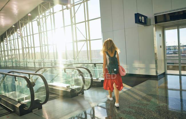 Vista trasera de la encantadora mujer rizada en falda roja con mochila caminando por las escaleras mecánicas en el aeropuerto de Texas - foto de stock