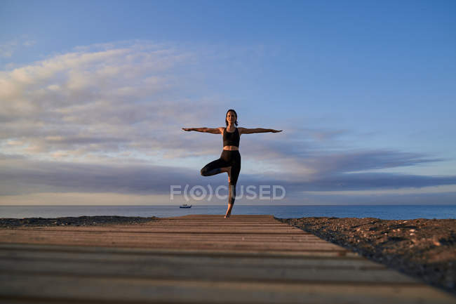 Вид сзади женщина в спортивной одежде, стоящая в позе дерева на песчаном пляже рядом с машущим морем вечером — стоковое фото