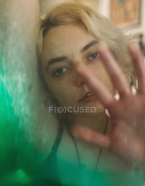 Женщина с карими глазами, смотрящая на камеру и мечтая при прикосновении к прозрачной поверхности с зеленым переходом — стоковое фото