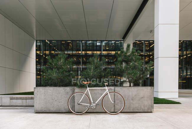 Велосипед припаркований на тротуарі біля стіни сучасного будинку в сонячний день на вулиці міста — стокове фото