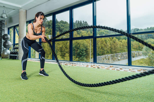 Focused strong woman in sportswear doing exercise with battle ropes during training in modern gym — Stock Photo