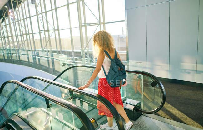 Vista lateral de la encantadora mujer rizada en falda roja con mochila caminando por las escaleras mecánicas en el aeropuerto de Texas - foto de stock