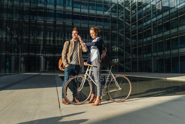 Веселые мужчина и женщина с велосипедом улыбаются и смотрят друг на друга, общаясь за пределами офисного здания на современной городской улице — стоковое фото