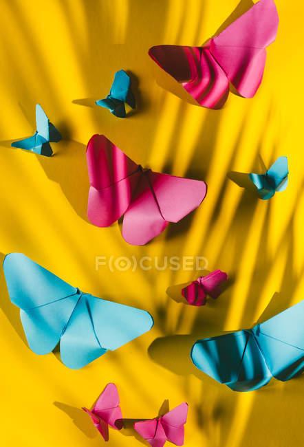 Borboletas frágeis feitas de papel com sombra de folha de palmeira ligada ao fundo de papelão amarelo — Fotografia de Stock