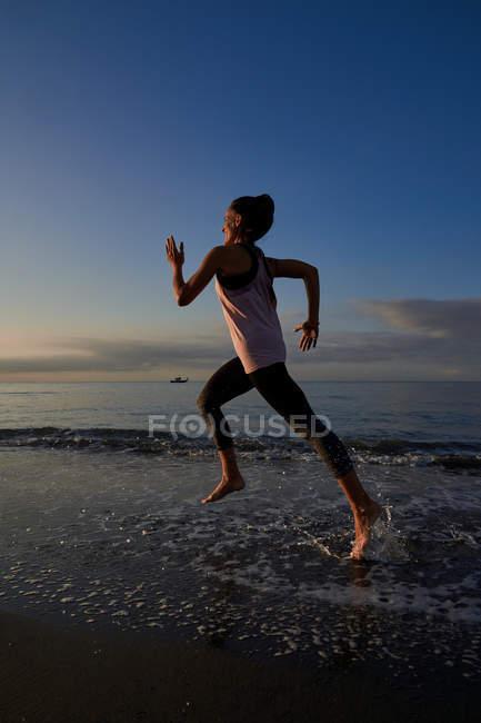 Вид сбоку на стройную женщину, бегущую по песчаному берегу у моря во время вечерней тренировки — стоковое фото