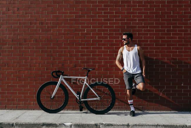 Cycliste masculin moderne détendu en vêtements de sport et lunettes de soleil reposant à côté de la bicyclette tout en se tenant debout sur une jambe et penché dos et pied sur un mur de briques rouges — Photo de stock