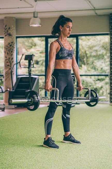 Мускулиста жінка у спортивному ласі піднімає важкий дзвін і озирається під час тренувань у спортзалі — стокове фото