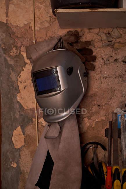 Сварочный шлем с защитными кожаными перчатками и фартуком, висящими на лоскутной коричневой стене рядом с рабочими инструментами — стоковое фото