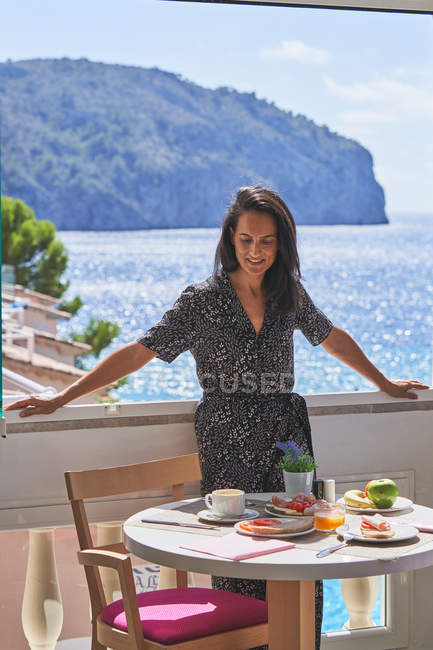 Thoughtful woman standing nearby window enjoying shiny calm water in light cozy terrace — Stock Photo