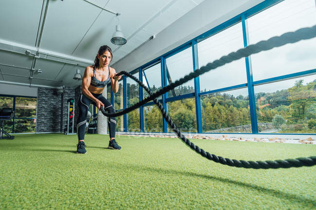 Full length focused strong woman in sportswear doing exercise with battle ropes during training in modern gym — Stock Photo