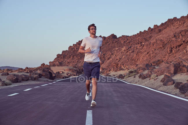 Satisfied man in glasses and casual clothes looking away while running on empty roadway with El Teide volcano and rocky cliffs around — Stock Photo