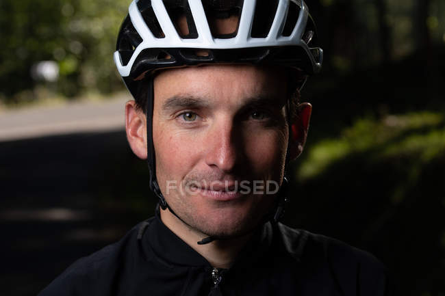 Positive cyclist looking at camera in park — Stock Photo