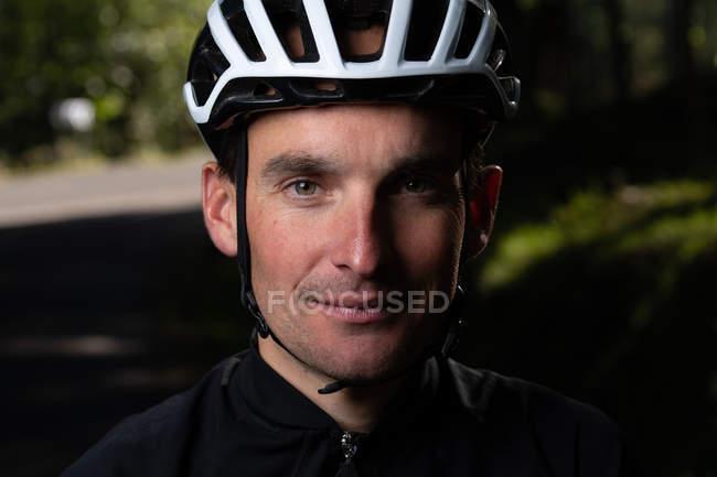 Cycliste positif regardant la caméra dans le parc — Photo de stock