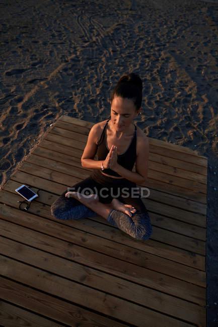 De arriba descalzo mujer en el sudor deportivo sentado en loto posan en el camino de madera cerca de los zapatillas y teléfono inteligente y meditación. - foto de stock
