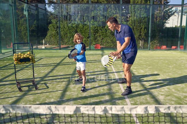 Homme adulte montrant au garçon comment tenir la pagaie et frapper la balle pendant l'entraînement de tennis par une journée ensoleillée sur le terrain — Photo de stock