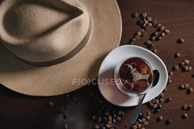 Glass of hot drink in composition with hat and coffee grains on wooden table — Stock Photo