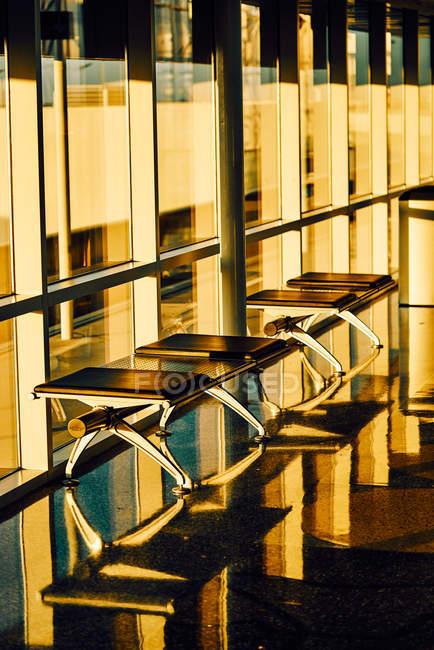 Banco de metal com bancos pretos de couro ao longo da parede de vidro no corredor ensolarado do aeroporto no Texas — Fotografia de Stock