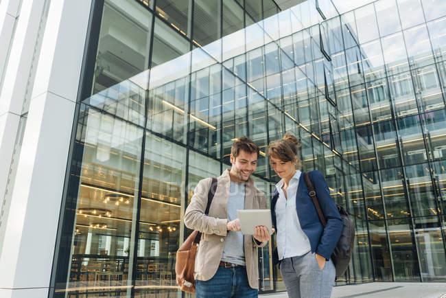 Optimiste hommes d'affaires souriant et naviguant sur tablette tout en se tenant à l'extérieur du bâtiment moderne et se reposant après le travail — Photo de stock