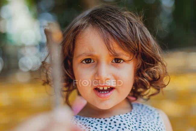 Bambino attivo che gioca con foglie gialle e bastone — Foto stock