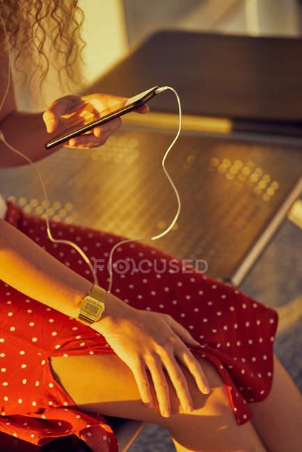 Обрезанный образ женщины в наушниках, слушающей музыку с мобильного телефона во время охлаждения на металлической скамейке в аэропорту Техаса — стоковое фото