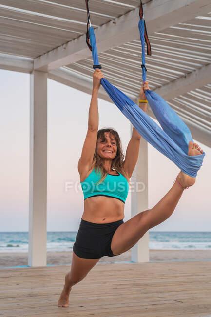 Спортивная силовая женщина, выполняющая растяжку с помощью гамака для воздушной йоги на деревянном стенде на песчаном пляже — стоковое фото