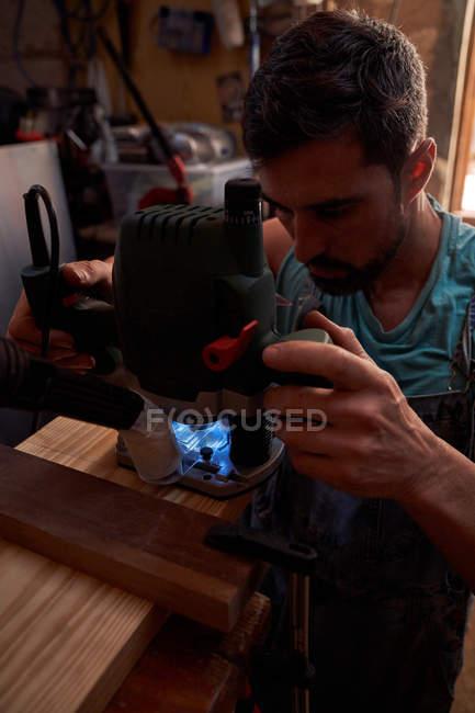 Tischler bearbeitet Holzdetails mit Fräsmaschine bei der Arbeit in der Werkstatt — Stockfoto