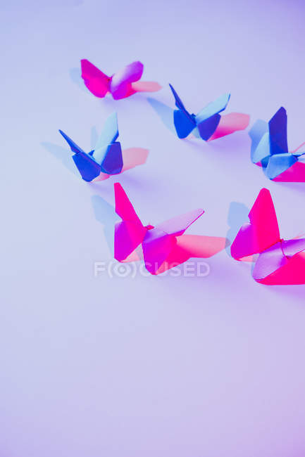 Pink and blue butterflies attached to lilac wall over carved paper leaf — Stock Photo
