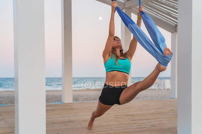 Fröhliche Frau streckt Bein auf blauer Hängematte für Luft-Yoga auf Holzbühne — Stockfoto