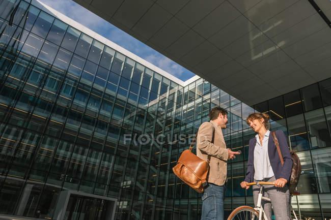 Веселый мужчина и женщина с велосипедом улыбаются и смотрят друг на друга, общаясь за пределами офисного здания на современной городской улице — стоковое фото