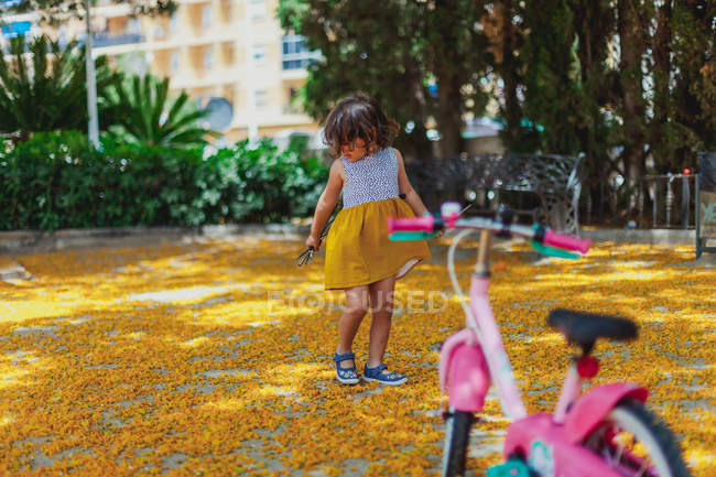 Active kid playing with yellow leaves and stick — Stock Photo