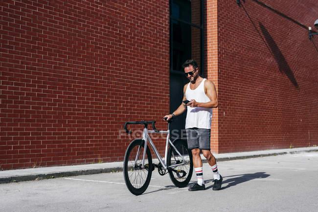 Bello ciclista di sesso maschile in abbigliamento sportivo e occhiali da sole utilizzando smartphone mentre in piedi con la bicicletta accanto al muro di mattoni rossi — Foto stock