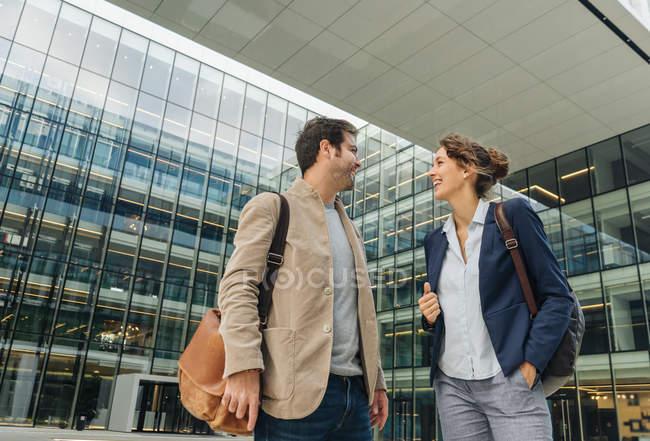 Восхищенные коллеги улыбаются и смотрят друг на друга, гуляя после работы за пределами современного здания — стоковое фото