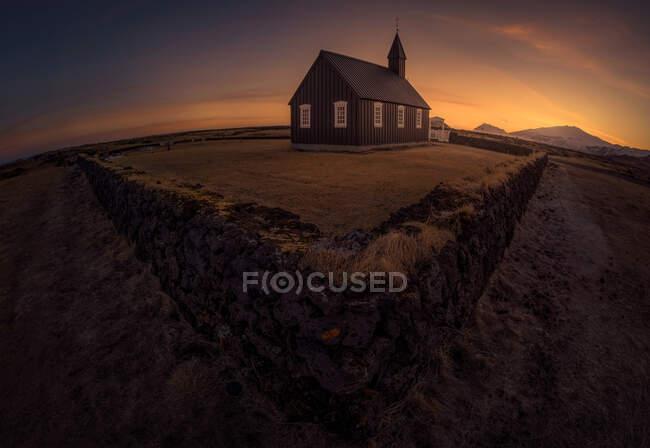 Semplice edificio della chiesa situato dietro la vecchia recinzione in pietra contro il luminoso cielo al tramonto in Islanda — Foto stock