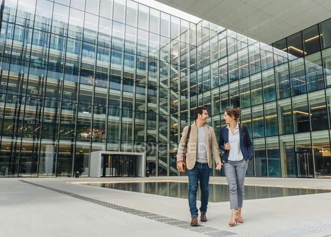 Ganzkörper entzückte Kollegen, die sich nach Feierabend beim Gang vor das moderne Gebäude anlächelten und ansahen — Stockfoto