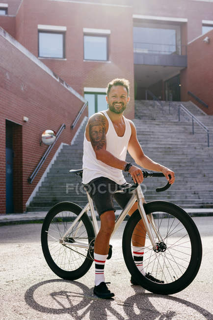 Sportive man wearing white sleeveless shirt and black shorts sitting on bicycle between buildings near stairs on summer sunny day — Stock Photo