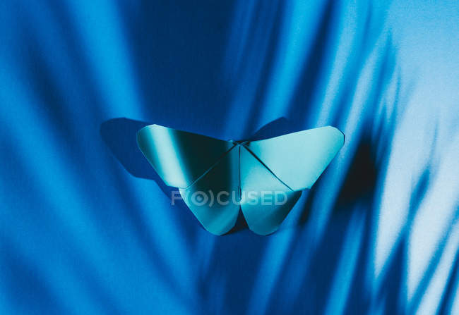 Fragile blue butterfly made of paper with palm tree leaf shadow attached to blue silk fabric — Stock Photo