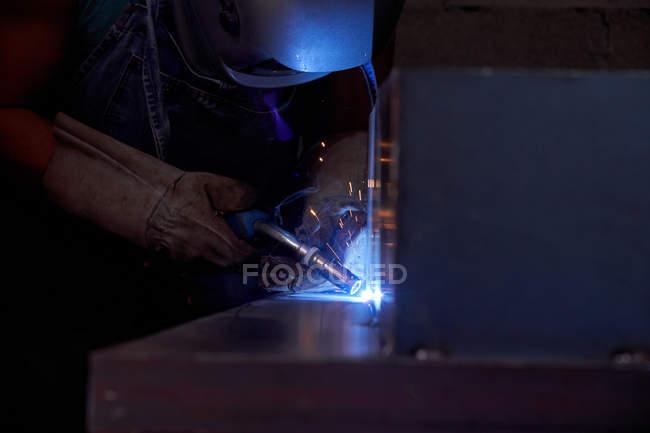 Бічний вид ремісника в захисній масці обличчя, одягнений в комбінезон і рукавички, які працюють в майстерні і паяння металевих конструкцій. — стокове фото