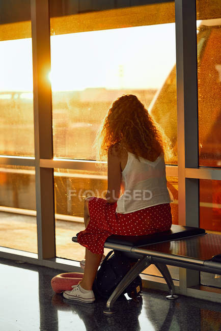 Woman sitting on metal bench in glass hallway of airport in Texas — Stock Photo