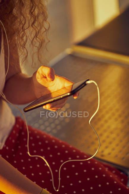 Abgeschnittenes Bild einer Frau mit Kopfhörer, die mit ihrem Handy Musik hört, während sie auf einer Metallbank im Flughafen von Texas chillt — Stockfoto
