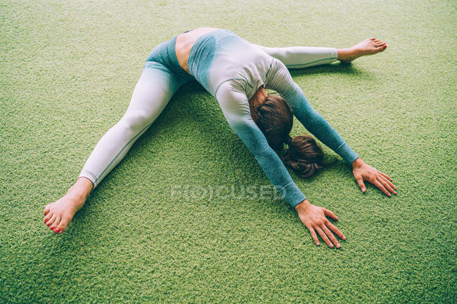 Dall'alto della donna in abbigliamento sportivo che si esibisce in avanti piegato con spacco mentre seduta sul tappeto verde durante l'allenamento in palestra — Foto stock