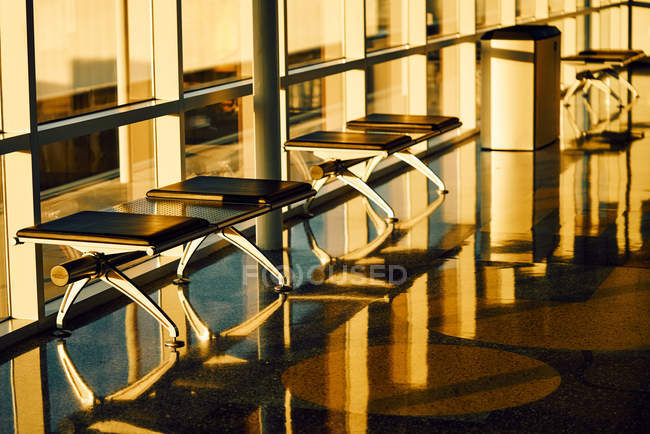 Metal bench with leather black seats along glass wall in sunny hallway of airport in Texas — Stock Photo