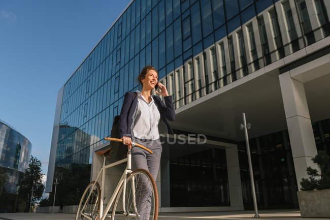 Femme d'affaires positive avec vélo souriant et parlant sur smartphone tout en marchant à l'extérieur du bâtiment contemporain par une journée ensoleillée sur la rue de la ville — Photo de stock