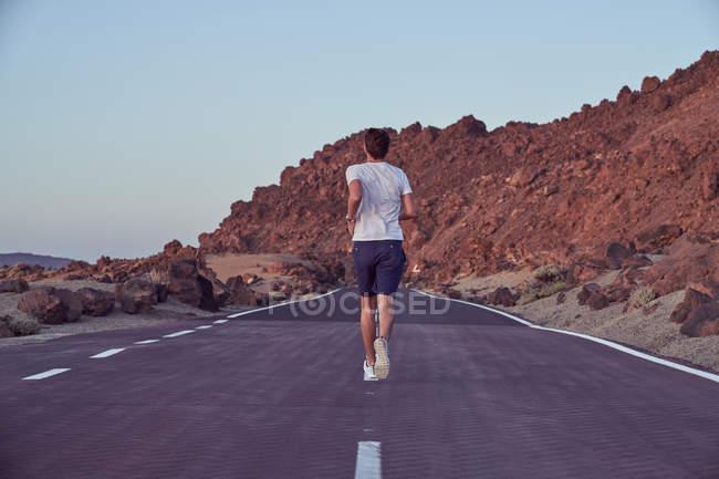 Человек в повседневной одежде бегает по пустой проезжей части с вулканом Эль-Тейде и скалами вокруг — стоковое фото