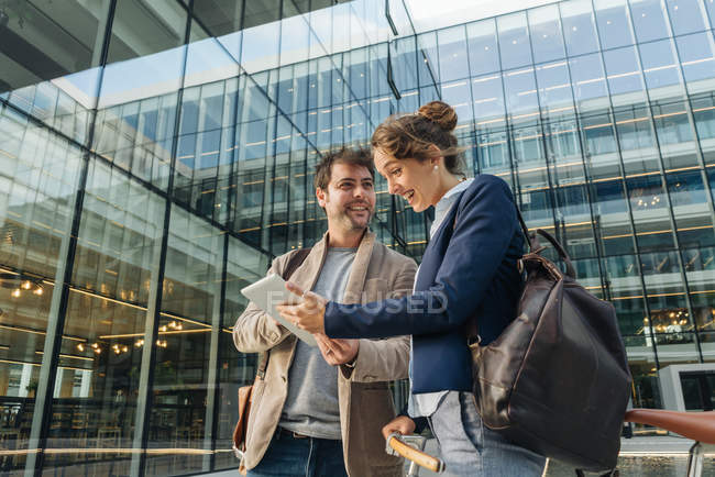 Optimistic businesspeople smiling and browsing on tablet while standing outside modern building and resting after work — Stock Photo